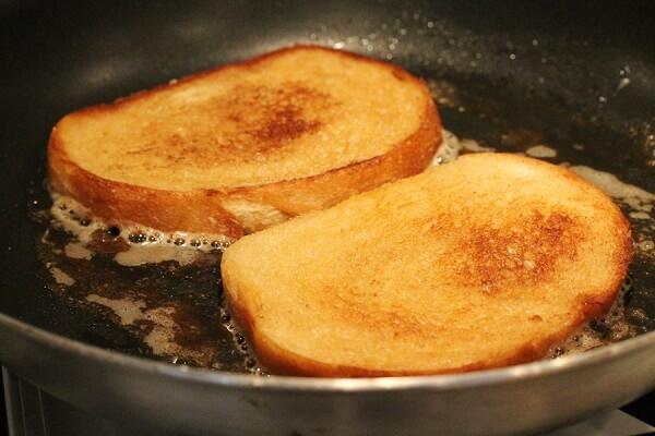 Đậy chảo lại và để cho bánh mì được nướng cháy phần cạnh