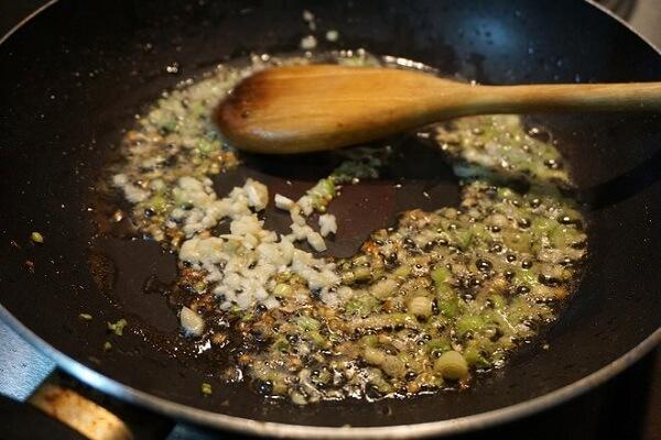 Đun nóng dầu ăn trên bếp, cho hành tỏi vào phi thơm lên
