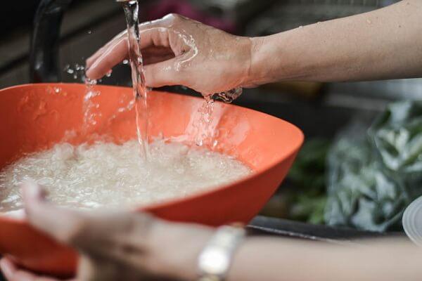Cho 2 chén gạo vào nồi, đổ nước vào vo sạch