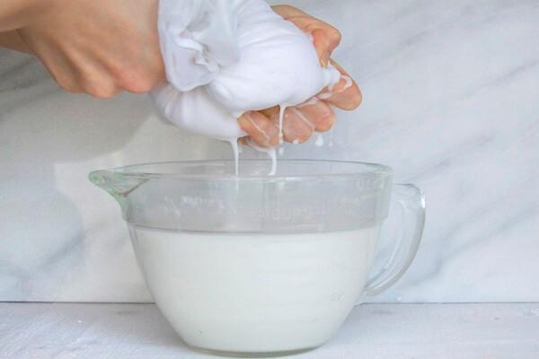 Dừa nạo cho vào bát nhỏ, đổ thêm một chút nước ấm