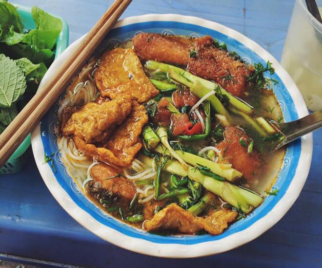Bát bún cá nóng ăn kèm với sa tế chua cay, rau sống