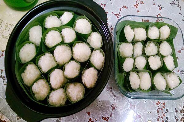 Nhúng tay vào bát nước muối ấm đã chuẩn bị sau đó lấy từng phần cơm nhỏ
