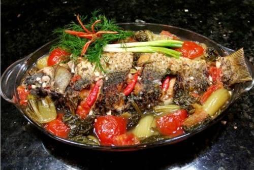 Khi cá còn lại khoảng 1/3 nước, bạn tắt bếp và cắt hành cho lên mặt