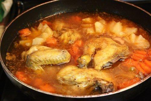 Thịt gà gần mềm, thì cho khoai tây và cà rốt vào, và tiếp tục nấu.