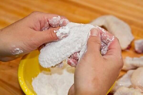 Gà sau khi ướp xong, cho vào tô bột mì, xóc đều