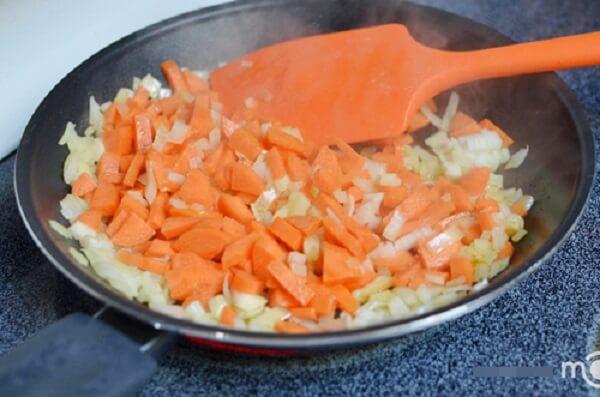 Đun nóng dầu ăn rồi cho hành tây, cà rốt vào xào cho đến khi mềm và có màu vàng nâu