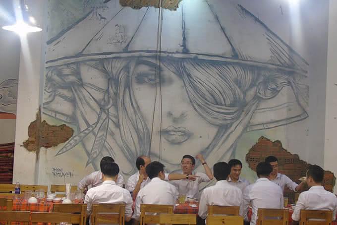 """Bức tường gạch còn nguyên """"dấu ấn xưa cũ"""" được trang trí bởi những bức tranh ấn tượng về người phụ nữ Việt"""