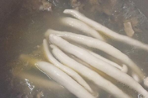 Nấm linh chi trắng thả vào nồi nước dùng.