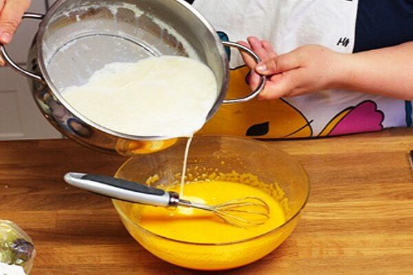 Đổ từ từ hỗn hợp sữa và kem tươi vào âu trứng