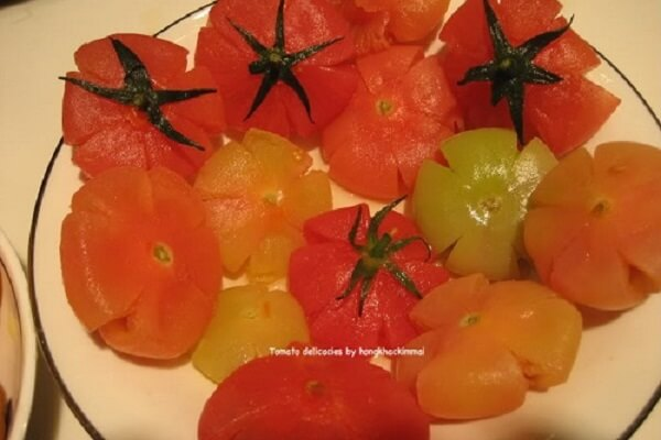 Với cách làm mứt cà chua ngon, bạn cần ép cho hạt cà chua ra hết và quả tạo thành hình bông hoa đẹp mắt