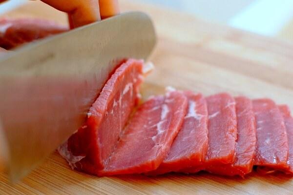 Dùng dao sắc để thái thịt bò thành từng lát mỏng