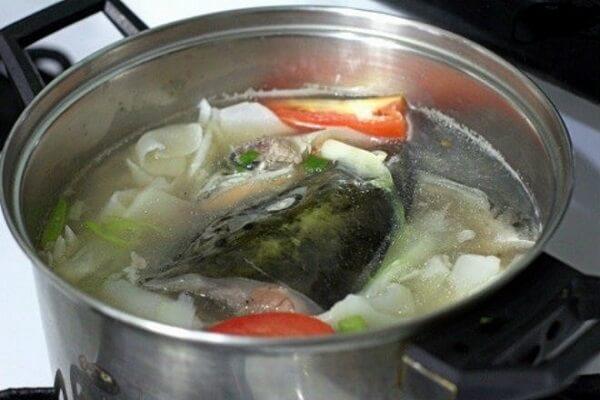 Khi canh sôi cho đầu cá hồi, măng chua, cà chua vào.