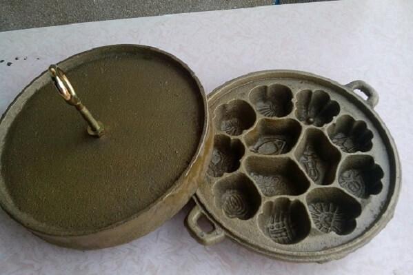 Đặt khuôn làm bánh lên bếp than đã được chuẩn bị sẵn.