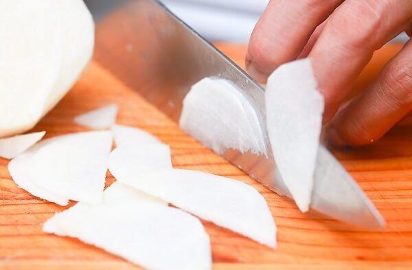 Dùng dao cắt củ đậu thành những miếng nhỏ