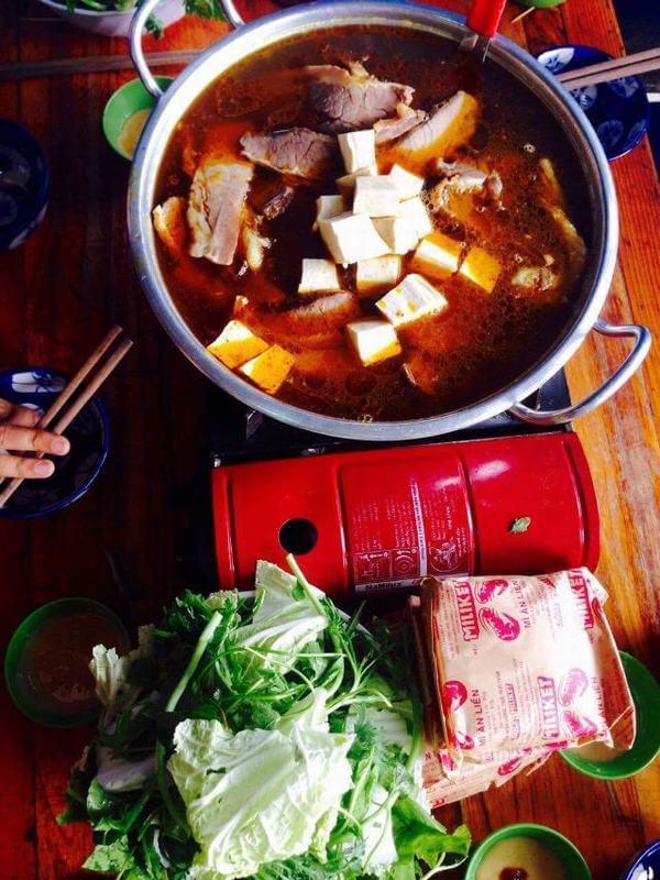 Một nồi lẩu to cùng với rau ăn kèm, mì tôm, đậu phụ cùng thịt bò to miếng