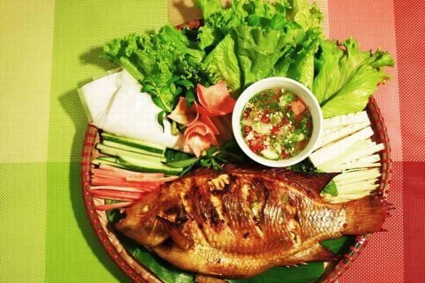 Thưởng thức món cá nướng thành phẩm với bún và các loại rau thơm